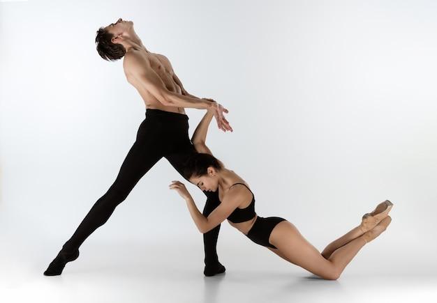Dwóch wdzięcznych tancerzy baletowych mężczyzna i kobieta w minimalistycznym czarnym stylu tańca na białym tle
