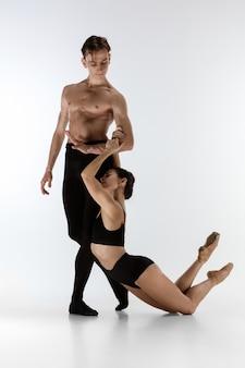 Dwóch wdzięcznych tancerzy baletowych mężczyzna i kobieta w minimalistycznym czarnym stylu tańczącym na białym tle