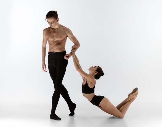 Dwóch wdzięcznych tancerzy baletowych mężczyzna i kobieta w minimalistycznym czarnym stylu tańczy na białym tle