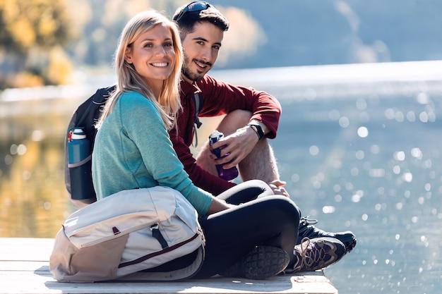 Dwóch wędrowców podróży patrząc na kamery, podziwiając przyrodę w jeziorze górskim.