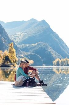 Dwóch wędrowców podróży za pomocą telefonu komórkowego, siedząc nad jeziorem w górach.