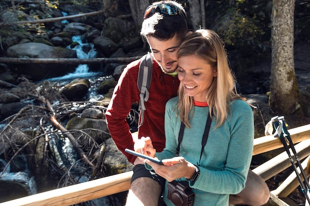 Dwóch wędrowców w podróży odbywa konsultację za pomocą telefonu komórkowego na drewnianym moście w lesie.