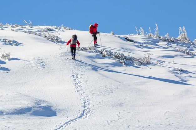 Dwóch wędrowców z plecakami wspinających się po zaśnieżonym zboczu góry