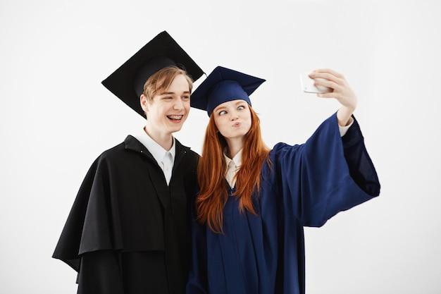 Dwóch wesołych absolwentów uniwersyteckiego oszukiwania, robiąc selfie.