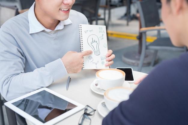 Dwóch wesołych azjatyckich ludzi biznesu dyskutujących z dokumentami
