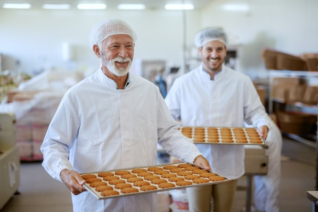 Dwóch wesołych kaukaskich pracowników niosących tace ze świeżymi ciasteczkami. oboje byli ubrani w białe sterylne mundury i mieli siatki na włosy. wnętrze zakładu spożywczego.