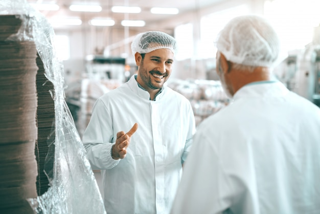 Dwóch wesołych kaukaskich pracowników zakładu spożywczego w białych mundurach iz siatkami na włosy stoi i rozmawia o produkcji żywności.