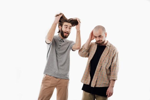Dwóch wesołych mężczyzn robi grymasy, włosy, pojedyncze białe miejsca, miejsca kopiowania