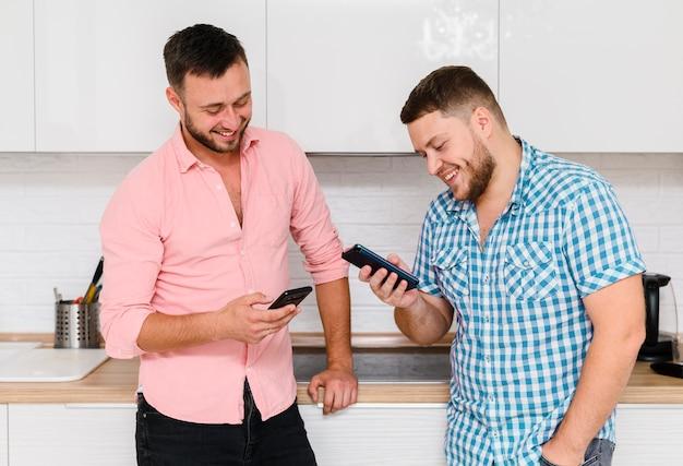 Dwóch wesołych młodych ludzi patrząc na smartfony