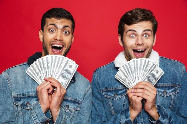 Dwóch wesołych młodych mężczyzn stojących na białym tle nad czerwoną ścianą, trzymając banknoty pieniędzy