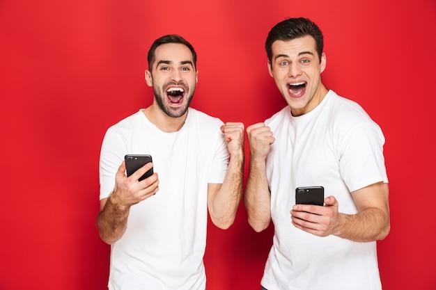 Dwóch wesołych podekscytowanych przyjaciół w pustych koszulkach, stojących na białym tle nad czerwoną ścianą, korzystających z telefonów komórkowych, świętujących sukces