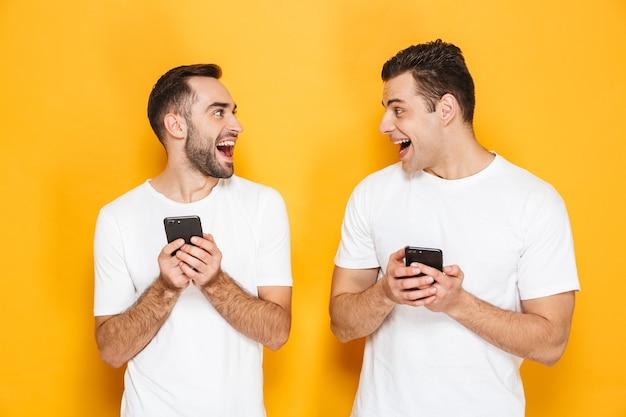 Dwóch wesołych podekscytowanych przyjaciół w pustych koszulkach stojących na białym tle nad żółtą ścianą, korzystających z telefonów komórkowych