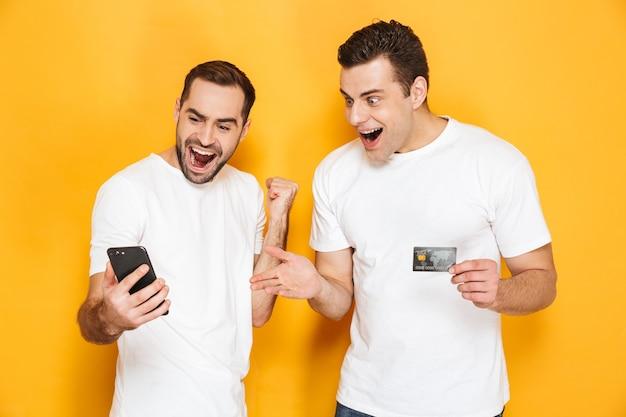 Dwóch Wesołych Podekscytowanych Przyjaciół W Pustych Koszulkach, Stojących Na Białym Tle Nad żółtą ścianą, Patrzących Na Telefon Komórkowy, świętujących Sukces Premium Zdjęcia