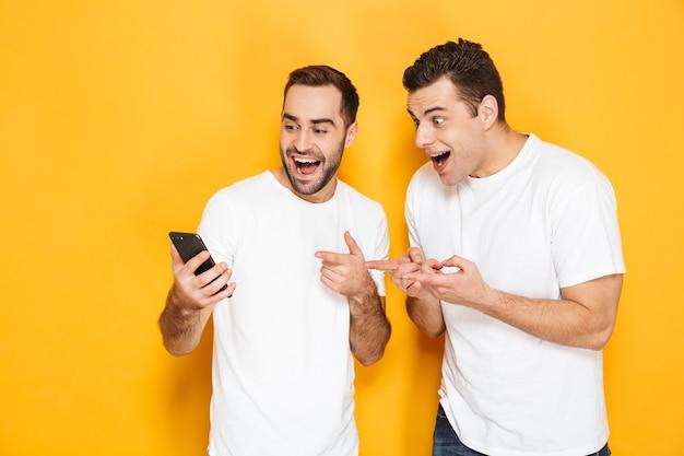 Dwóch wesołych podekscytowanych przyjaciół w pustych koszulkach stojących na białym tle nad żółtą ścianą, patrzących na telefon komórkowy, świętujących