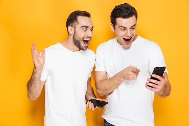 Dwóch wesołych podekscytowanych przyjaciół w pustych koszulkach stojących na białym tle nad żółtą ścianą, używających telefonów komórkowych, świętujących sukces