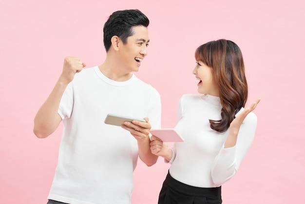 Dwóch wesołych przyjaciół stojących na białym tle na różowym tle, grając w gry na telefonie komórkowym.