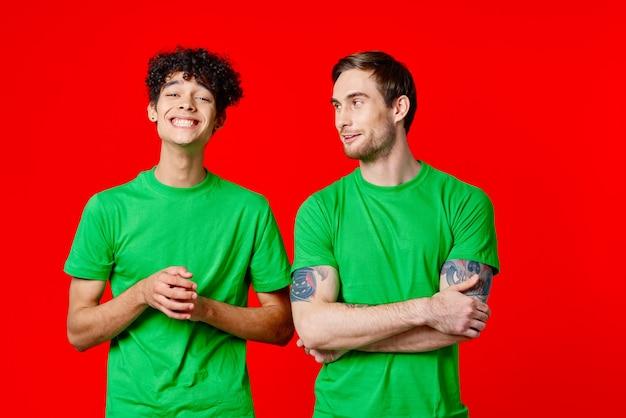 Dwóch wesołych przyjaciół w zielonych koszulkach komunikujących emocje na czerwonym tle