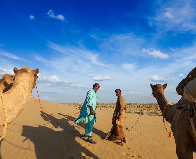 Dwóch wielbłądów (kierowców wielbłądów) z wielbłądami na wydmach thar