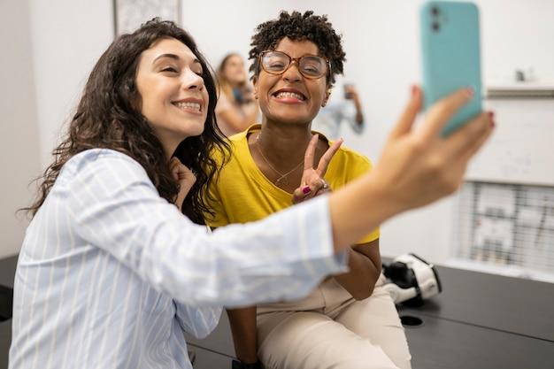 Dwóch wielorasowych przyjaciół robi sobie selfie ze współpracownikiem
