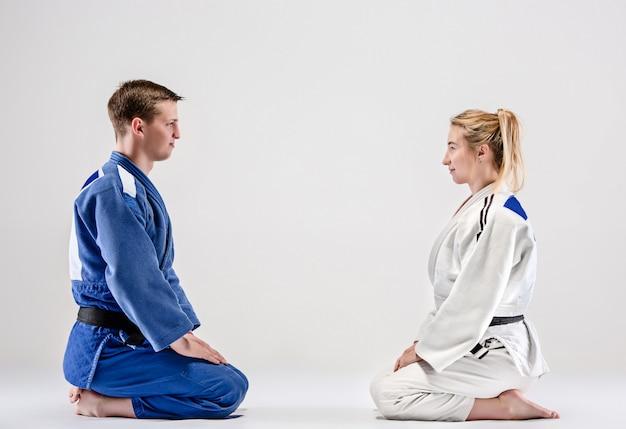 Dwóch wojowników judoków pozujących na szaro