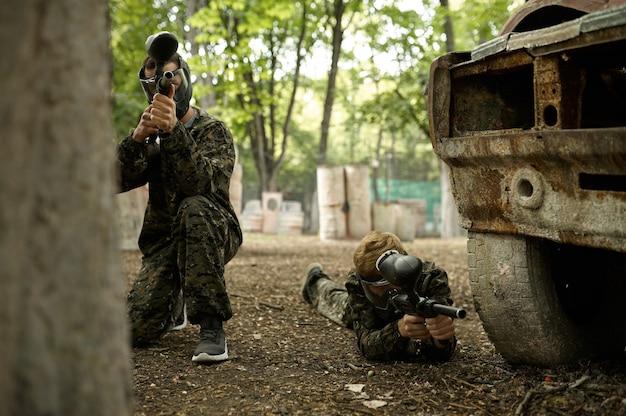 Dwóch wojowników płci męskiej w kamuflażach i maskach celujących z pistoletów paintballowych