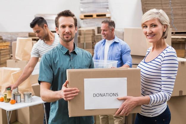 Dwóch wolontariuszy posiadających pudełko darowizn