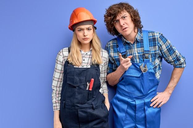Dwóch wściekłych budowniczych niezadowolonych z terminu pracy patrzy w kamerę z niezadowolonym wyrazem twarzy