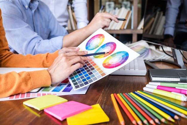 Dwóch współpracowników kreatywnych grafików pracujących nad wyborem kolorów i próbkami kolorów