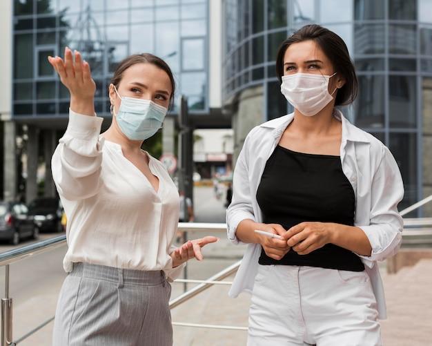 Dwóch współpracowników na zewnątrz podczas pandemii w maskach