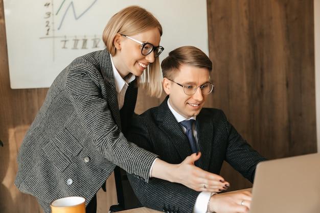 Dwóch współpracowników patrzy na dokumenty i pracuje na laptopie, kierownik sekretarki lub kobieta czyta dokument, uśmiechnięta bizneswoman.
