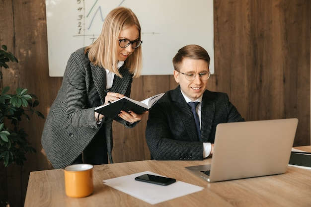 Dwóch współpracowników pracuje na laptopie, sekretarka lub menadżerka czyta dokumenty. praca zespołowa w biurze.