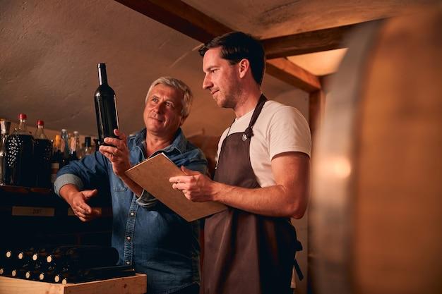Dwóch wykwalifikowanych pracowników winnicy stojących w piwnicy i patrzących na jedną z nieoznakowanych butelek wina