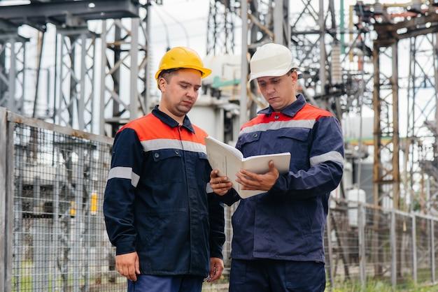 Dwóch wyspecjalizowanych inżynierów elektroenergetycznych kontroluje nowoczesny sprzęt wysokiego napięcia. energia. przemysł.