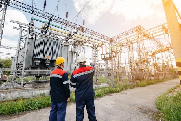 Dwóch wyspecjalizowanych inżynierów elektroenergetycznych kontroluje nowoczesny sprzęt wysokiego napięcia podczas zachodu słońca. energia. przemysł.