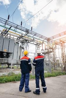 Dwóch wyspecjalizowanych inżynierów elektroenergetycznych kontroluje nowoczesny sprzęt wysokiego napięcia podczas zachodu słońca.