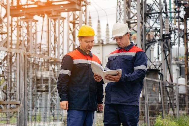 Dwóch wyspecjalizowanych inżynierów elektroenergetycznych wieczorem wieczorem sprawdza nowoczesny sprzęt wysokiego napięcia.