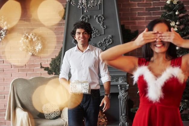 Dwóch z nich się uśmiecha. kobieta w czerwonej sukience otrzyma teraz prezent świąteczny od chłopaka.