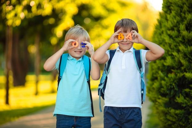 Dwóch zabawnych roześmianych chłopców uczniów z literami w rękach.