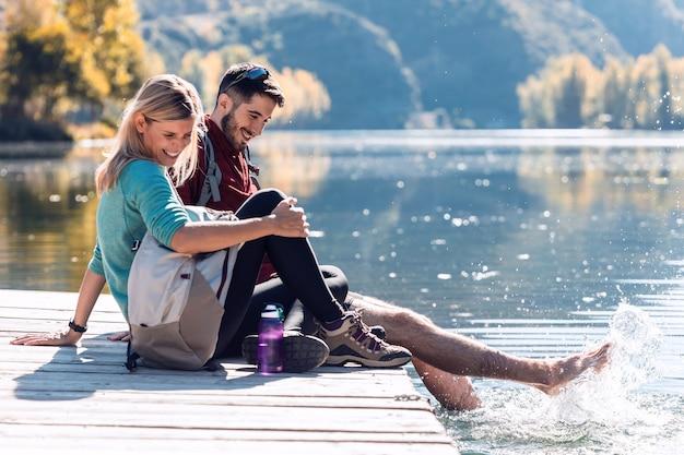 Dwóch zakochanych wędrowców, którzy cieszą się przyrodą i bawią się wodą w jeziorze górskim.