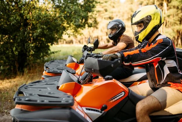 Dwóch zawodników atv w kaskach przed podróżą, widok z boku, lato las na tle. mężczyźni - kierowcy quadów, jazda na quadach, aktywne podróżowanie