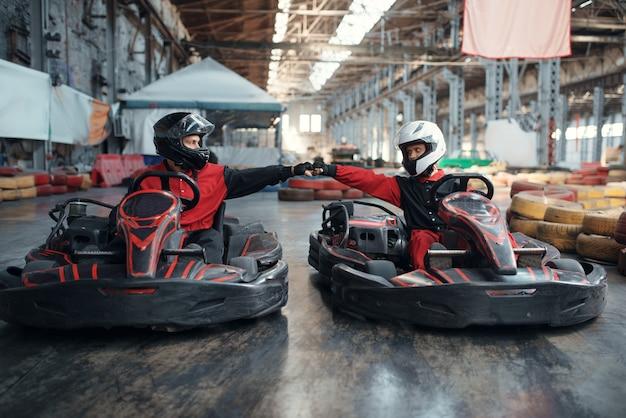 Dwóch zawodników gokartów na linii startu, widok z przodu, karting auto sport indoor. wyścig szybkościowy na bliskim torze gokartowym z barierą dla opon. szybka rywalizacja samochodowa, pełen adrenaliny wypoczynek