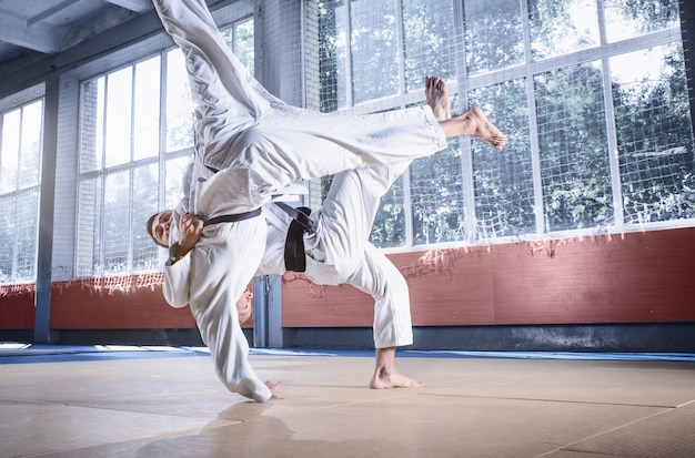 Dwóch zawodników judo wykazujących się umiejętnościami technicznymi podczas treningu sztuk walki w klubie walki. dwaj wysportowani mężczyźni w mundurach. walka, karate, trening, sztuka, sportowiec, koncepcja zawodów