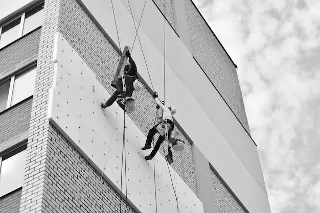 Dwóch zawodowych mężczyzn izoluje budynek mieszkalny na zewnątrz. alpinizm przemysłowy. dwóch wspinaczy izoluje ścianę domu na linach.