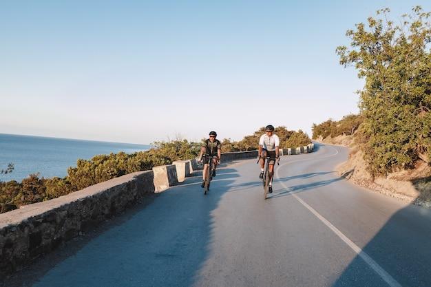 Dwóch zawodowych rowerzystów płci męskiej jadących rano razem na rowerach wyścigowych po przybrzeżnej drodze