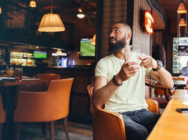 Dwóch zrelaksowanych brodatych mężczyzn siedzących w barze i zamawiających jeszcze jedną szklankę piwa