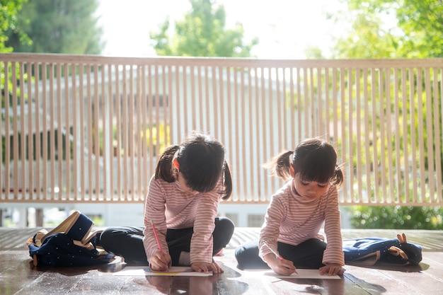 Dwoje azjatyckich dzieci odrabiających razem lekcje w domu