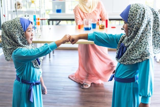 Dwoje azjatyckich dzieci użyło ręki do uderzenia pięścią, aby pokazać swoją współpracę do sukcesu w klasie