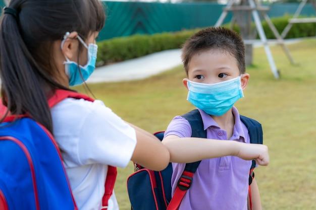 Dwoje azjatyckich przyjaciół w wieku przedszkolnym spotyka się w parku szkolnym zamiast powitania uściskiem lub uściskiem dłoni zamiast tego uderzają łokciami.