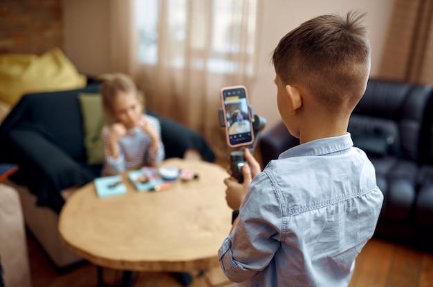 Dwoje blogerek dziecięcych nagrywa bloga kamerą, mali vlogerzy. blogowanie dzieci w domowym studio, media społecznościowe dla młodych odbiorców, transmisja internetowa w internecie
