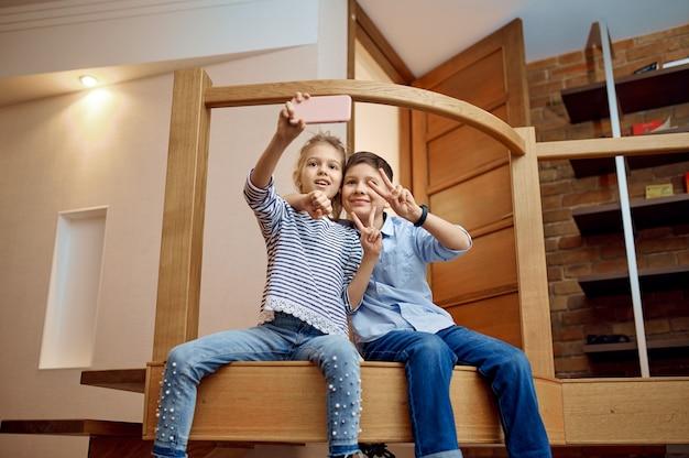 Dwoje blogerek dziecięcych robi selfie aparatem w telefonie, mali vlogerki. blogowanie dzieci w domowym studio, media społecznościowe dla młodych odbiorców, transmisja internetowa w internecie